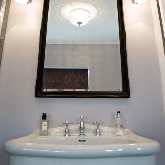 classic style basin and taps with mirror and wall lights