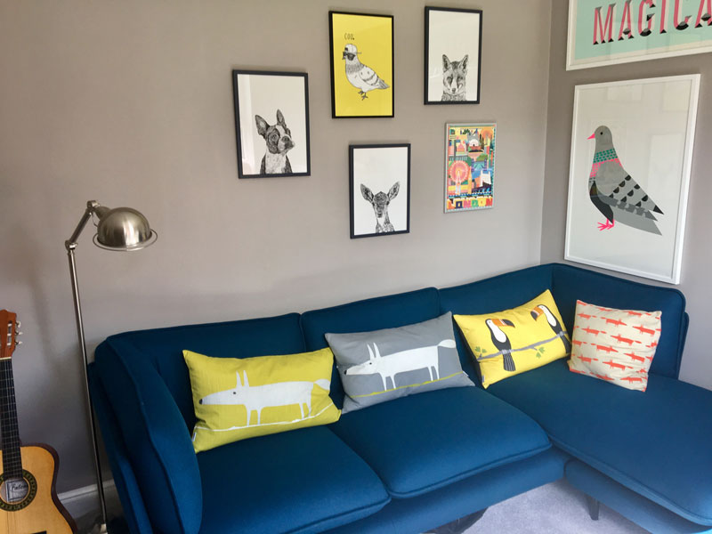 bright blue corner sofa with patterned cushions and graphic artwork