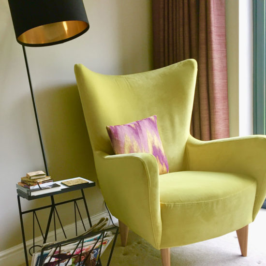 bright yellow armchair and modern floor light to create reading nook