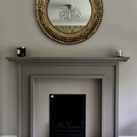 painted fireplace surround and decorative brass wall mirror