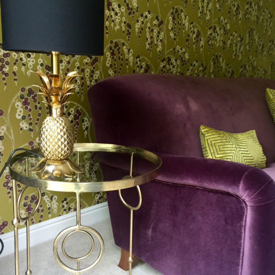 decorative floral wallpaper with purple velvet sofa and pineapple table lamp