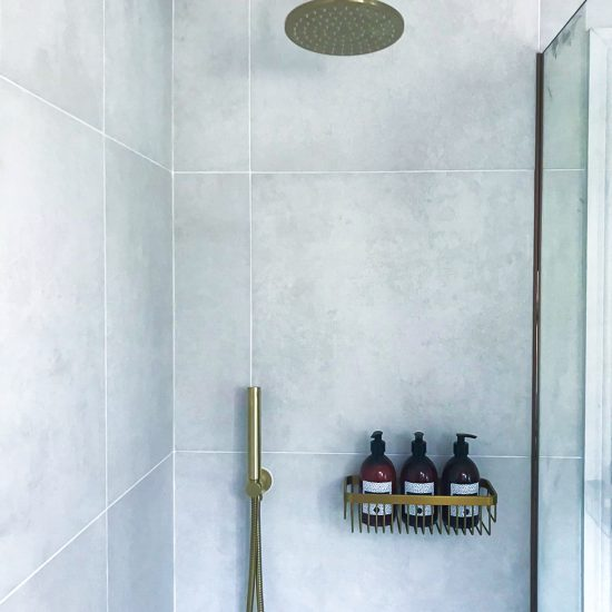 brushed brass shower area with white tiles